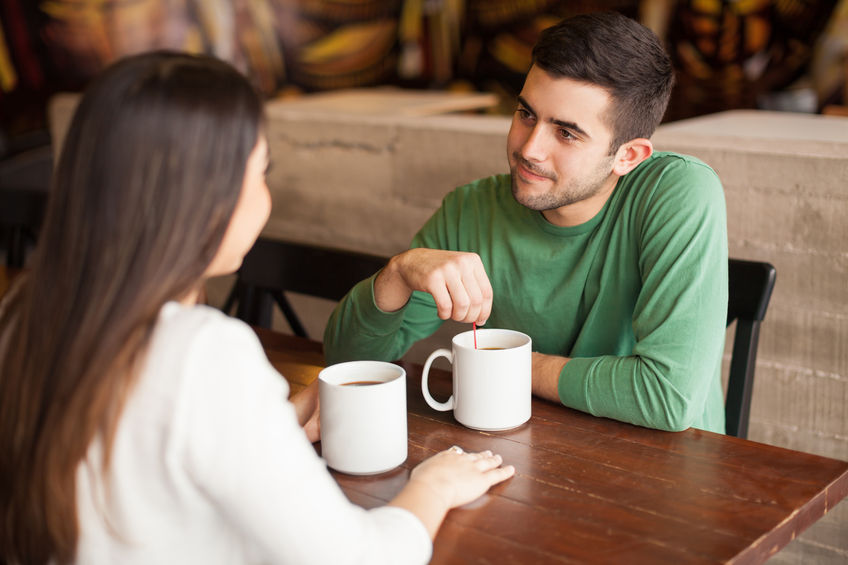 53298682 - handsome young man having a cup of coffee with a woman at a restaurant