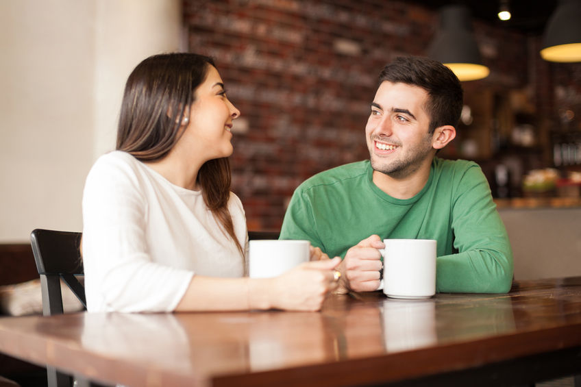 53298688 - cute happy couple enjoying a cup of coffee while on a date at a cafe
