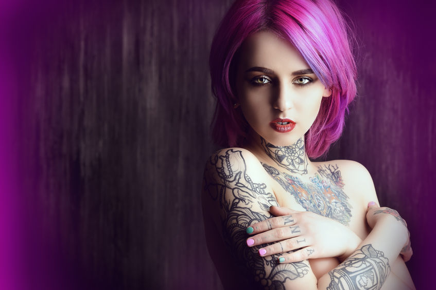 53482023 - beautiful young woman with stylish crimson hair and tattoo on her body posing over dark grunge background. hair coloring. cosmetics, make-up. tattoo.