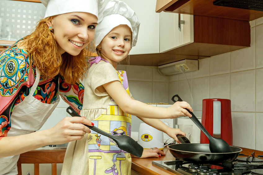 55053537 - mom and daughter in white chef hats cook in the kitchen. looking at the camera.