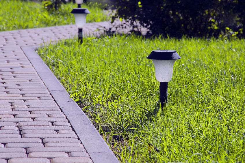 70001539 - garden lighting - lights on the solar battery on a green lawn next to a paved path