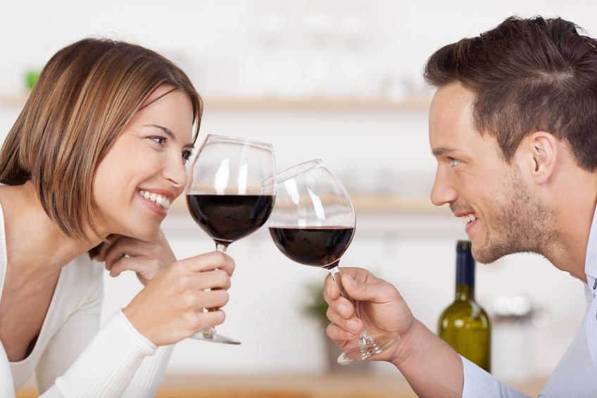 21162391 - happy couple toasting with red wine leaning towards each other smiling as they celebrate