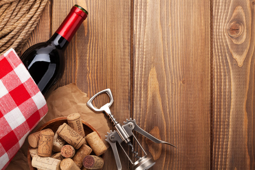 44050253 - red wine bottle, corks and corkscrew over wooden table background. top view with copy space
