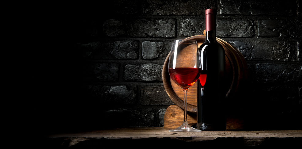 52587528 - red wine on a background of old black bricks