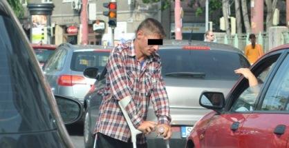 Bezdomovec žobre na križovatke a barle